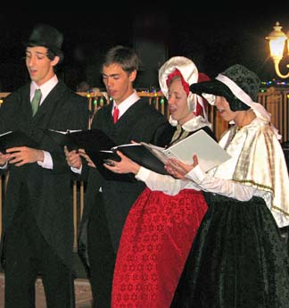 Four Christmas carolers (2 guys and 2 girls) singing at a local resort.