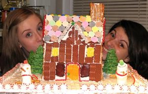 Two girls peeking out from behind a small gingerbread house.