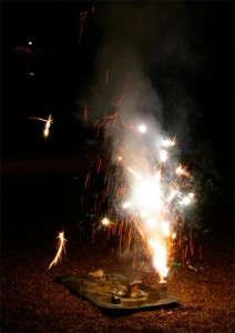 Ground fireworks shooting white sparks into the air.