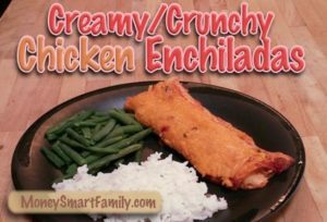 Black plate with white rice, green beans and a chicken enchilada covered with cheese.