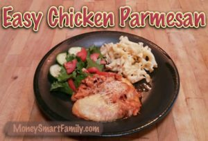 Black plate with a green salad, pasta and chicken parmesan on it.