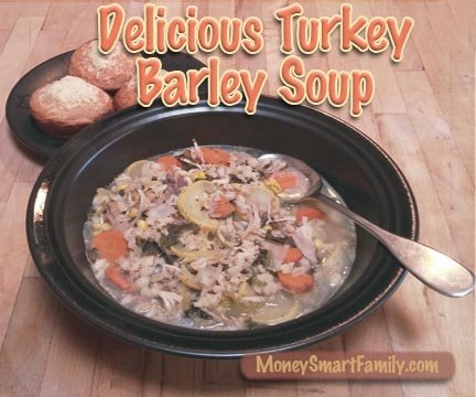 A black bowl filled with turkey barley soup and 3 cornbread muffins on another dish.
