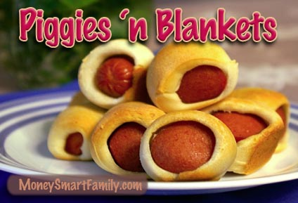 Piggies in blankets stacked on a white plate with blue trim.
