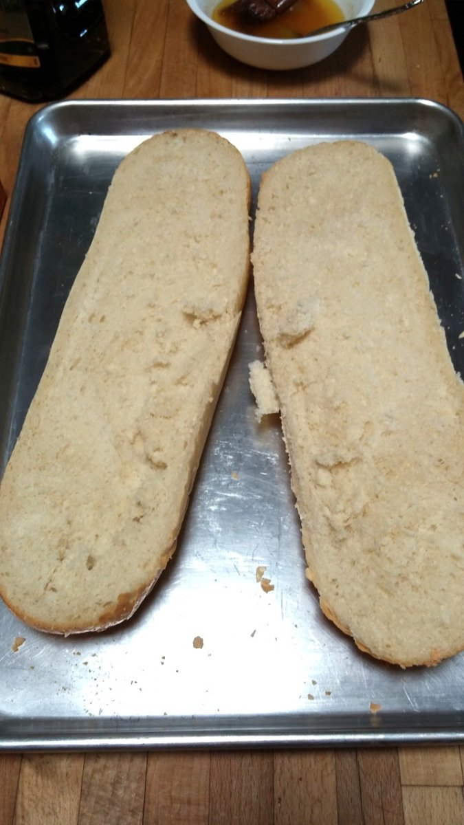 1 loaf of french bread cut in half length-wise to be made into garlic bread. Sitting on an aluminum cookie sheet.