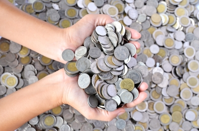 Child's hands holding handfuls of coins.