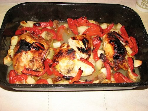 Chicken and peppers in a roasting pan to cook in the oven.