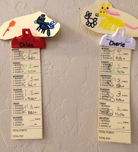 two paper time cards from MoneySmart Kids system hanging in plastic clips on the wall.