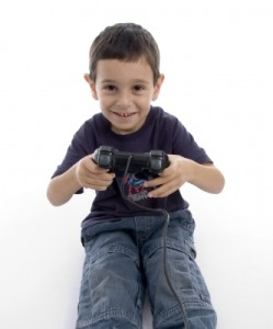 Toddler boy with a video controller in his hands, smiling.