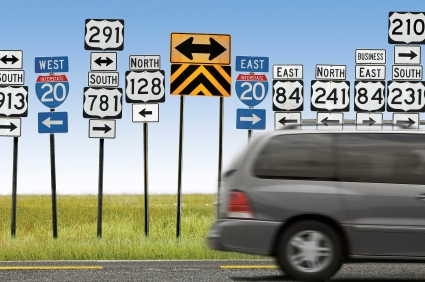 A gray mini van rushing past many highway directional signs.