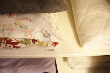 Bed linens stacked on a linen closet shelf.
