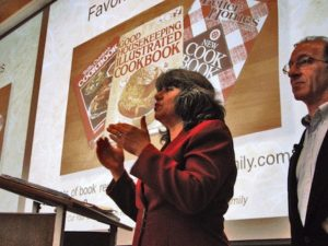 Annette Economides standing in front of a large slide image showing her three favorite cookbooks.