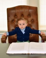 young boy sitting at a large business desk with a book opened in front of him