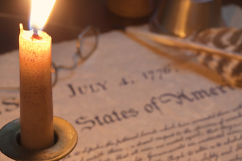 A lit candle sitting on the Declaration of Independence.