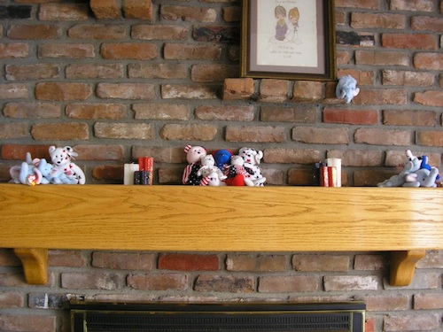 An oak mantle decorated with various beanie babies with red, white and blue candles.