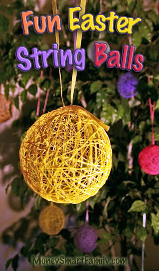 A Yellow string ball hanging from a yellow ribbon on a ficus tree, decorated for Easter.
