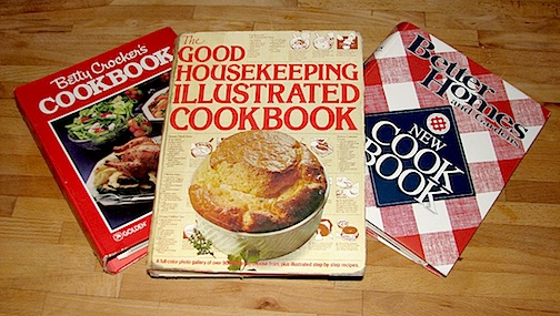 3 cookbooks on a butcher block counter. Better crocker, Good housekeeping and Better homes and gardens cookbooks.