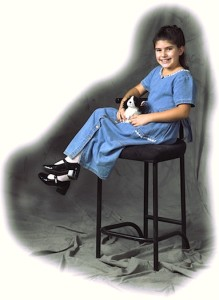 A young girl sitting in a high black chair, wearing a blue jean dress.