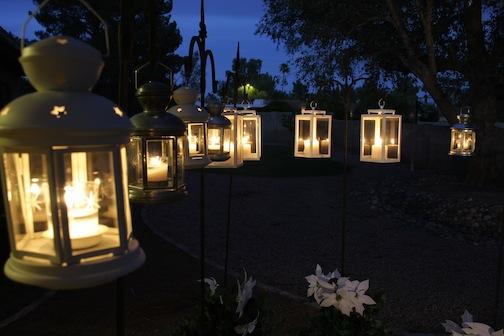 Eight white lanterns hanging on shepherds crooks with lit candles inside.
