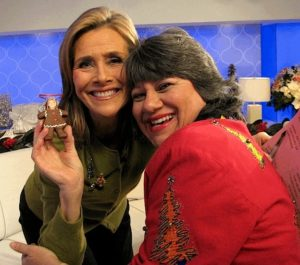 Meredith Viera with Annette Economides holding a brown gingerbread ornament.