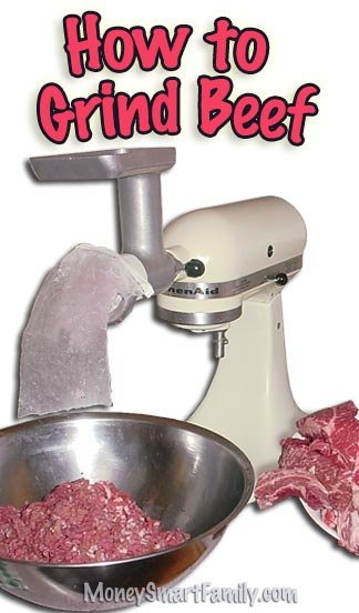 White kitchenaid mixer with a meat grinding attachment on top and a silver bowl full of red, ground beef below.