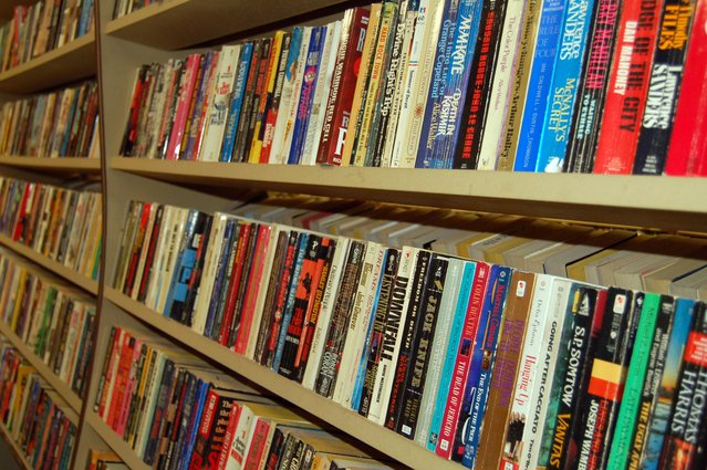 hundreds of paperback books on wooden shelves.