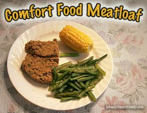 A white plate with green beans, half ear of corn and 2 slices of meatloaf.