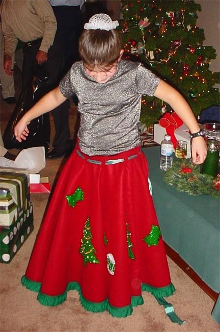 Abbey wearing a red and green Christmas tree skirt.