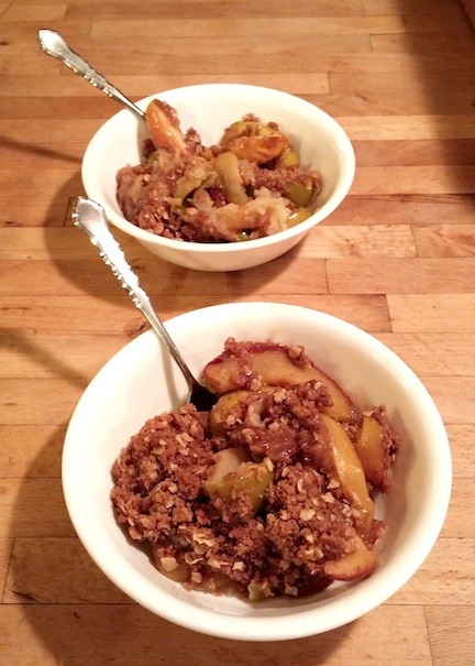 Two white bowls with apple crisp in them.