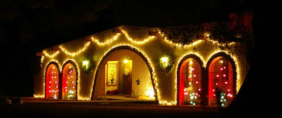 The front of a house with white and red Christmas lights on it.