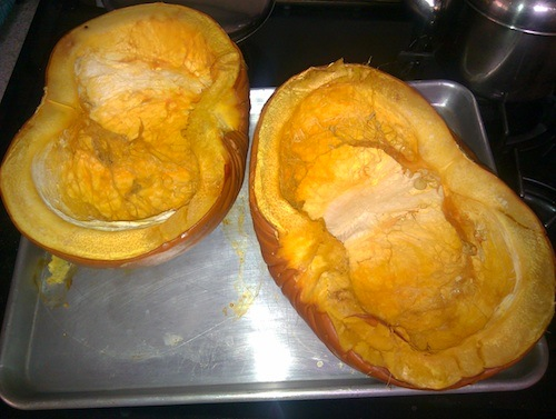 Two half pumpkins, cooked and sitting on an aluminum roasting pan.