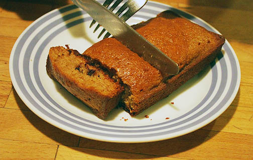 A silver knife and fork being used to cut a loaf of chocolate chip zucchini bread.