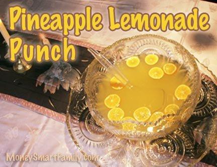 A punch bowl full of pineapple lemonade with lemons floating on top.