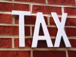 A red brick wall with a Tax sign on it.