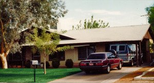 a brown house with a maroon car and a blue van parked in the drive way.