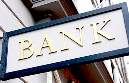 A grey bank sign with golden letters.