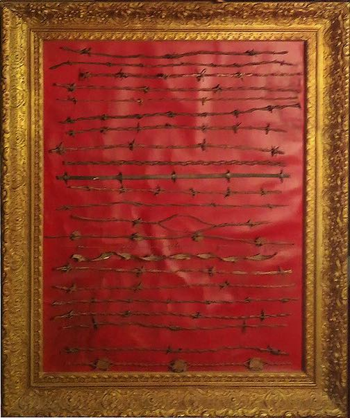 A golden picture frame with strands of barbed wired on a red background.