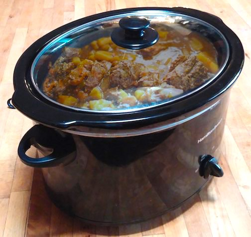 A black crockpot with beef stew in it.