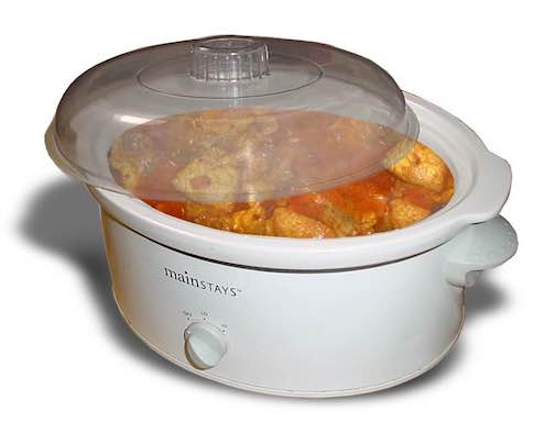 A white crockpot full of chicken marsalla.