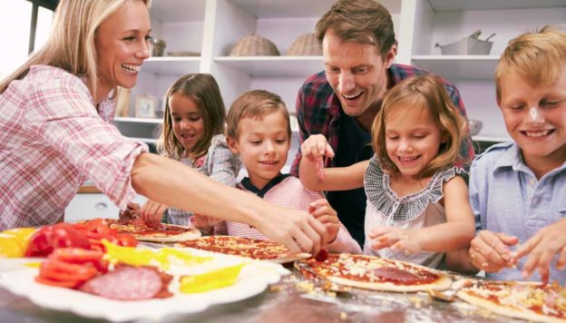 Around the dinner table: Making Eating Together Fun. A family making pizzas for dinner together.