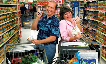 Steve & Annette Economides in the grocery store with walkie talkies.