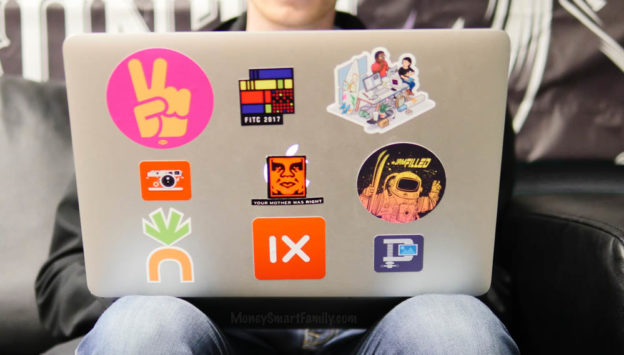 A mac laptop with free stickers on it.