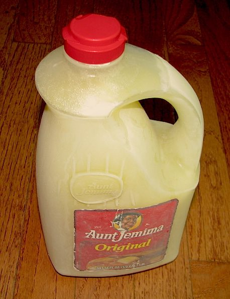 A half gallon of frozen milk in an Aunt Jemima syrup container