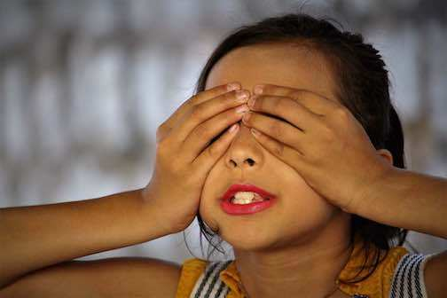 A girl covering her eyes guessing.