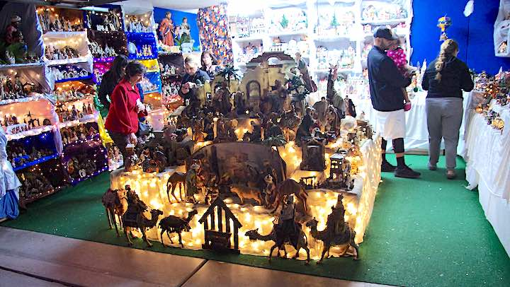 Many nativity scenes on display in a garage.
