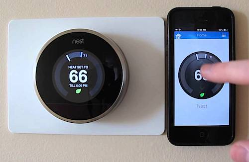 Nest Thermostat with a cell phone app next to it.