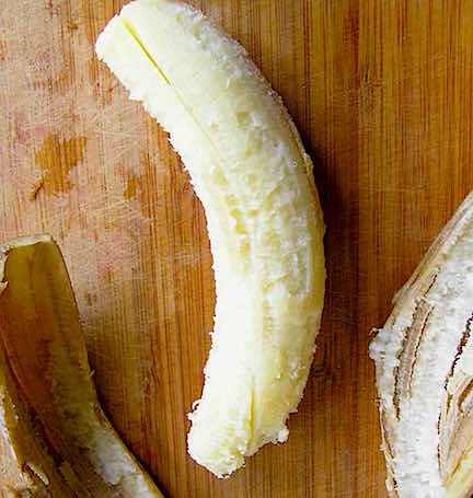 A peeled, over ripe banana on a wooden cutting board.