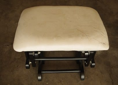 Microfiber Ottoman foot stool with ink stain scribbles on it.
