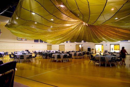 A large cargo parachute hung over a banquet hall. Indoor, Interesting Hobbies #ParachuteDecor #WeddingParachute #WeddingHallParachute #WeddingDecorParachute