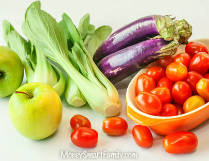 Colorful produce on a table, including apples, tomatoes, eggplant and bok chow.