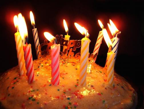A birthday cake with 10 lit candles on it.